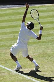 Tennis player serving in all white