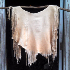 (front view)  A 1-hide no-yoke buckskin shirt, with extra fine fringe. From a white tail deer.  A row of stiches around the neck, and dyed accents were later added to this shirt.  Made 2016