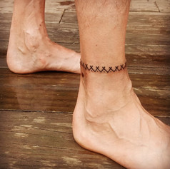 This ankle band motif was designed together by Victoria & the tattooee. This motif represents tipis and village.  This tattoo was done outdoors in one long session, of about 4-5 hours, alternating between a sewing needle and a hawthorn thorn.  Depending upon the skin and tolerance of the tattooee, a band of this size may take 2 or more sessions.  Appalachians of North Carolina, 2018.