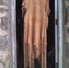This 2-hide buckskin dress was constructed from two braintanned doe skins, stitched with thong cut from the same hides, and dyed with black walnut husk.  2016
