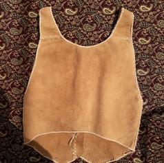 (back) buckskin vest with buckskin thong stitching & deer bone buttons. Dyed with black walnut husk. Spring 2020