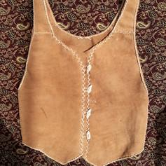(front) buckskin vest with buckskin thong stitching & deer bone buttons. Dyed with black walnut husk. Spring 2020