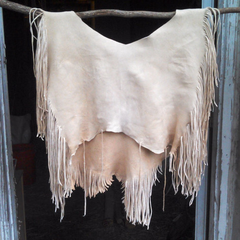 (back view)  A 1-hide no-yoke buckskin shirt, with extra fine fringe. From a white tail deer.  A row of stiches around the neck, and dyed accents were later added to this shirt.  Made 2016