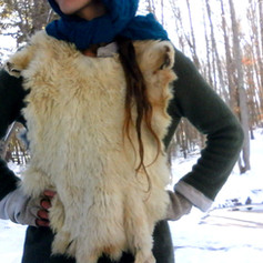 Here is an example of a simple, no-cut fur vest, which can be worn underneath an overcoat for extra insuation. It is made from 2 vegetable tanned domestic rabbit fur completely whole and uncut. The two hides (one on the front of the body and the other on the back of the body) are attached by buckin braiding which runs over each shoulder, and braided buckskin straps which can be tied together on either side of the torso, a ways down from the arm pits.  This vest is also reversible. It can be worn with the fur facing out or the fur facing in.  Sometimes very tailored garment designs make sense. But other times, the simplest constructions are both beautiful & practical.  I should have won an etsy award for how posh this photo is.   Made 2017