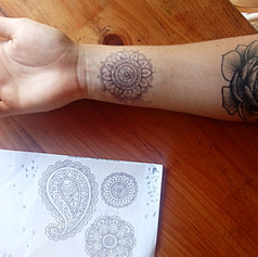 The previous motif before tattooing begins.   Shown here, first a design is freehand drawn onto the body, as a guide. Then the tattoo is dotted in with ink, and then fully tattooed.