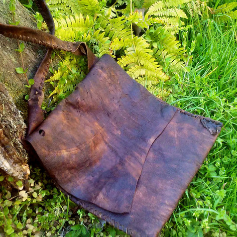 This simple, deer leather satchel was made from a scrap hide and Victoria's childish stitching skills.   Incredibly, after several years of rather heavy duty use (carrying jugs of water, over-stuffing the bag, leaving it in hot cars and scalding sandy beaches over multiple Summer seasons in Florida...) this bag has held up immaculately.   I have been shocked time and again by the lasting strength of natural leathers.  The dark, nearly purplish colors of this hide are due to being tanned with hemlock bark.  Also, stitching leather with leather thong always makes for the strongest seams. There's no need for special thread. On the occasion when you need to do very fine or nearly invisible stiching, sinew cannot be surpassed.  Made 2017