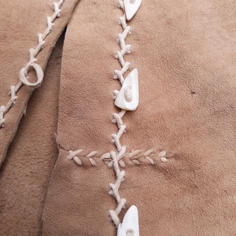buckskin vest with buckskin thong stitching & deer bone buttons