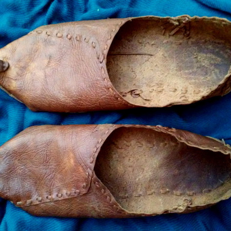 This pair of shoes is made from a white tail doe hide vegetable tanned using sumac and blackberry leaves.  The design of this shoe was inspired by relics of ancient Egyptian coptic leather slippers and modern day juutis of India. All stitching is with leather thong cut from the same hide.  Like Indian juutis, the two shoes are made in an identical shape, meaning there is no right and left sole. The supple leather quickly molds to the feet of the wearer, creating a perfect fit, literally like wearing a second skin.  This photo was taken after some wear to the shoes.  Made 2017