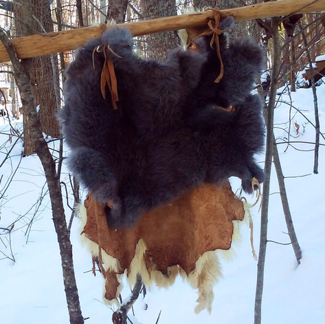 (Detail- back side)   Here is an example of a simple fur vest, which can be worn underneath an overcoat for extra insuation. It is made from 2 vegetable tanned domestic rabbit fur completely whole and uncut. The two hides (one on the front of the body and the other on the back of the body) are attached by buckin braiding which runs over each shoulder, and braided buckskin straps which can be tied together on either side of the torso, a ways down from the arm pits.  This vest is also reversible. It can be worn with the fur facing out or the fur facing in.  Sometimes very tailored garment designs make sense. But other times, the simplest constructions are both beautiful & practical.  I should have won an etsy award for how posh this photo is.   Made 2017