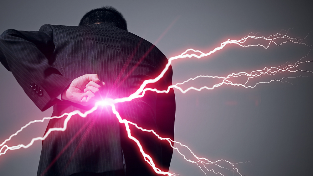 Man holding back with lightening bolts coming from his body indicating low back pain