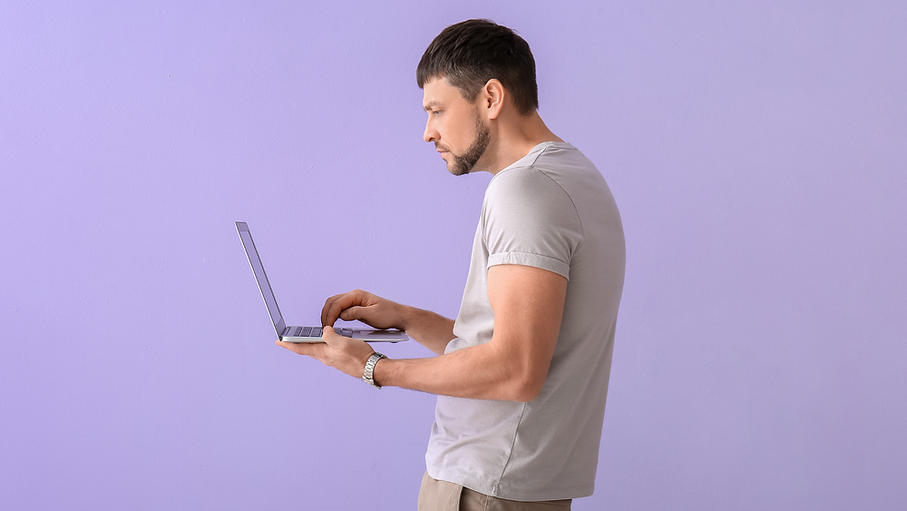 man standing and holding a lap top slouched with bad posture