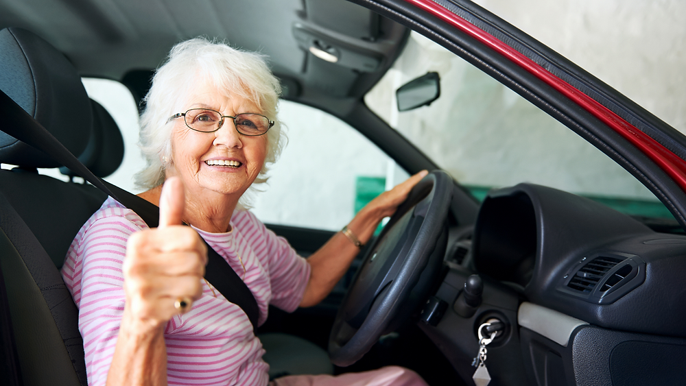 woman giving thumbs up from driver seat to indicate proper driving ergonomics
