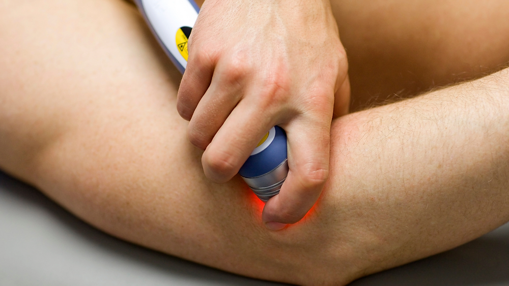 man receiving laser therapy on elbow pain