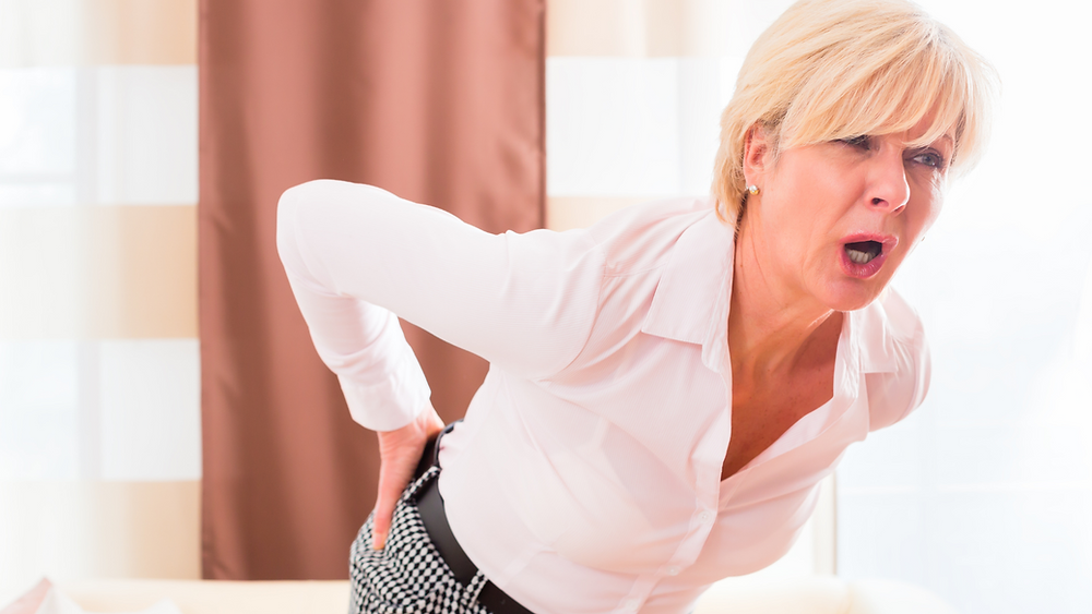 woman bent over holding back due to sciatic pain