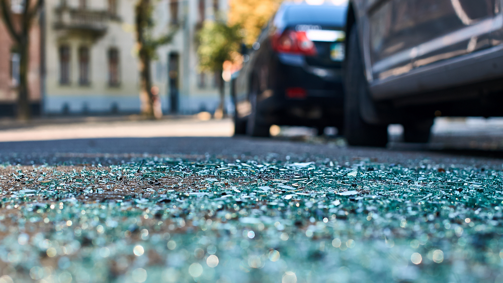 glass on road after car crash - seek chiropractic care