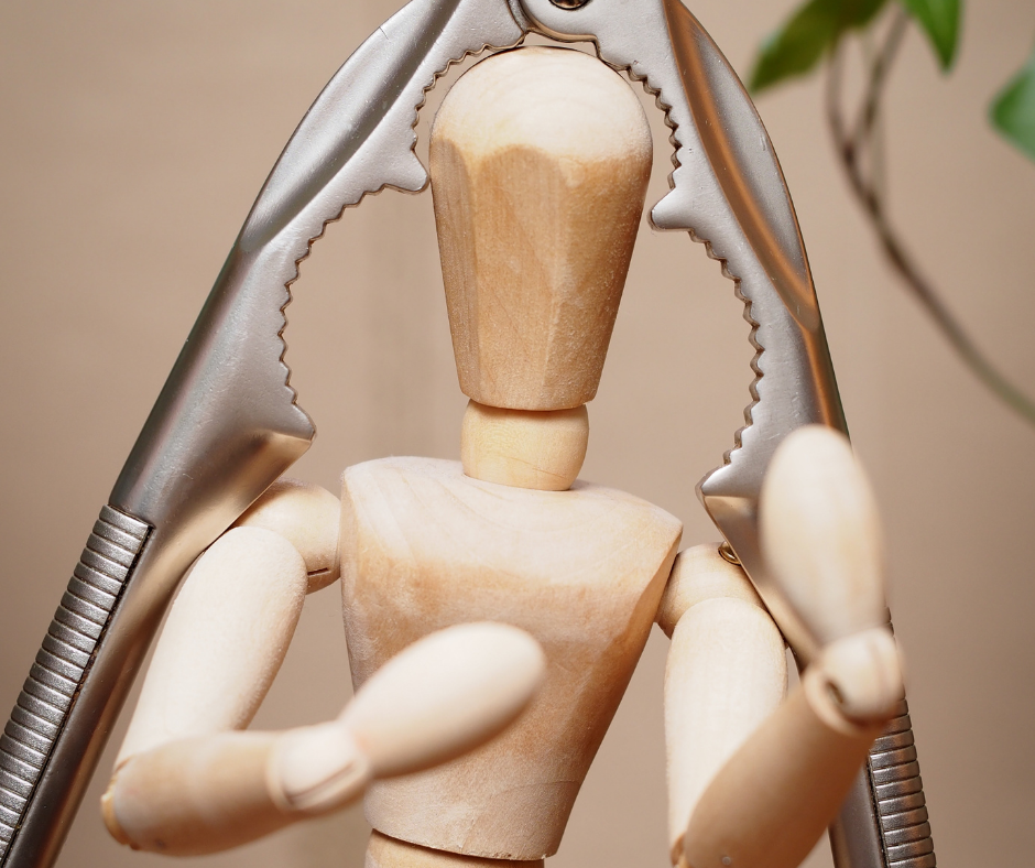 wooden figure of person with nut cracker over head depicting headache