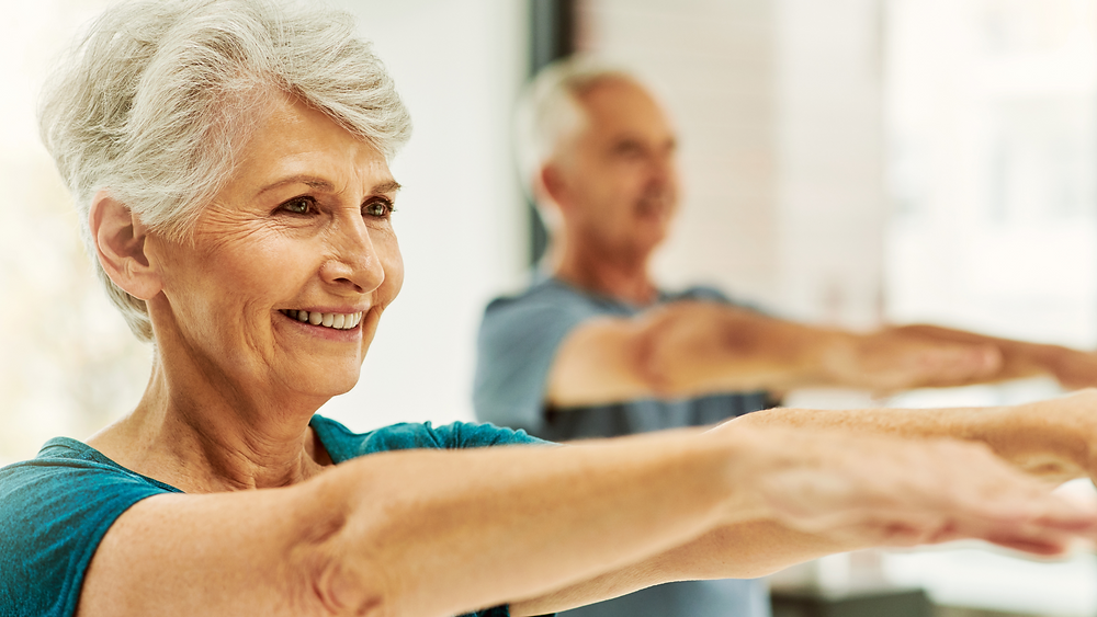 older man and woman doing stretching exercises for arthritis