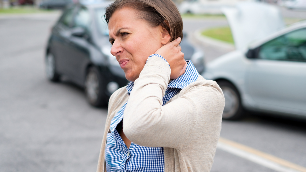woman holding neck for whiplash after car accident