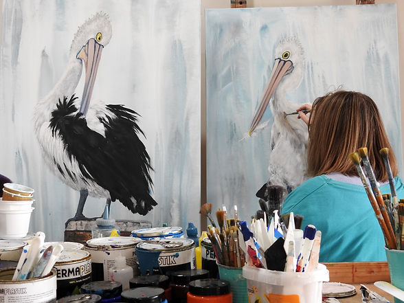 artist naomi veitch painting pelicans in art studio.jpg