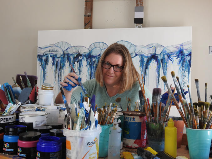 Naomi painting a large bluebottle painting in her studio 2021