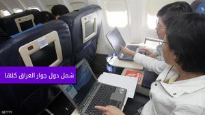 مسافرين يحملون اجهزة كمبيوتر في طائرة