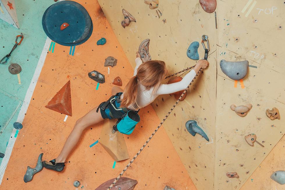 Teen girl climbing on artificial boulder