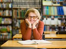 Happy senior woman in library..jpg