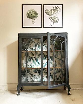 Vintage black glass cabinet with botanical print