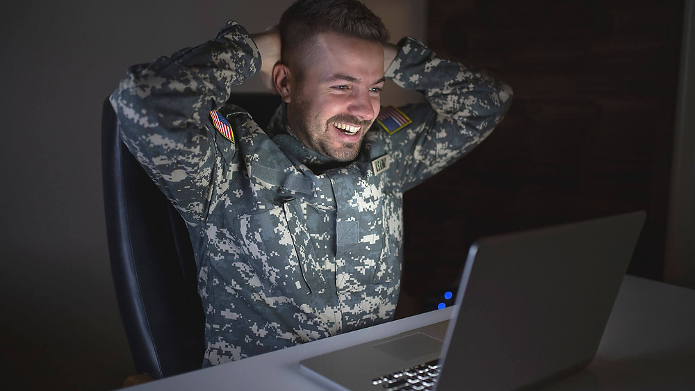 An army guy watching his vidday on a laptop