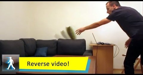Showing a reserve video of a guy throwing a pillow on a couch