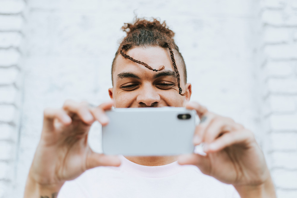 A guy taking a selfie with his phone