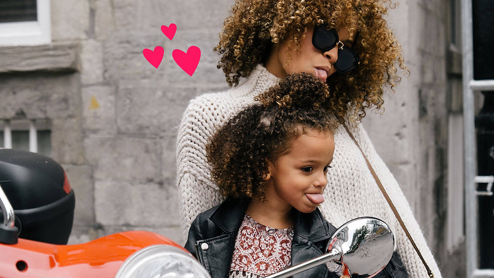 A Mom and Daughter are looking into a motorcycle review mirror. They are sticking out their tongues and are very happy! There are hearts coming from both of them because they love each other.