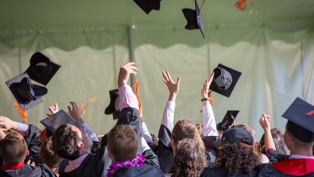 grads throwing their caps into the air at their graduation