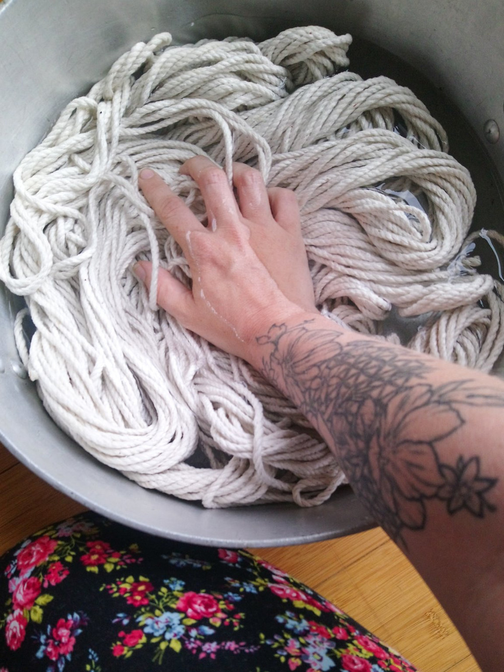 A photo of some rope submerged in water and being held down by a hand and tattooed arm.