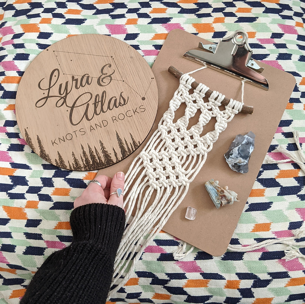 A mini macrame wall hanging on a clipboard, with a bright cushion, some crystals, a hand adorned with rings and a wooden logo.