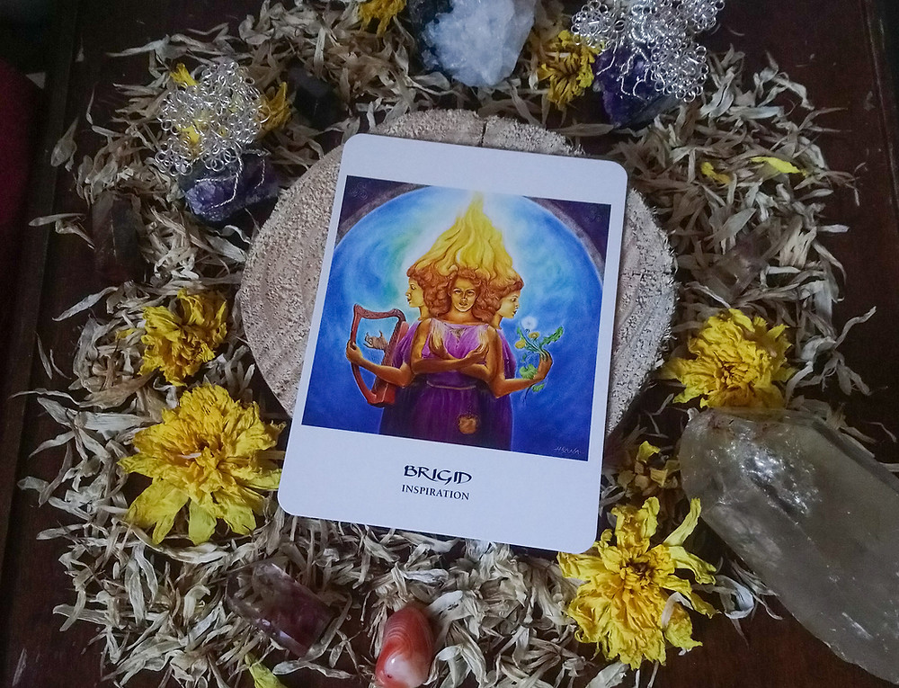 An oracle card showing Brigid, surrounded by flowers and crystals.