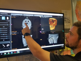X-ray technician demonstrating how the software for one of our refurbished CBCT units.