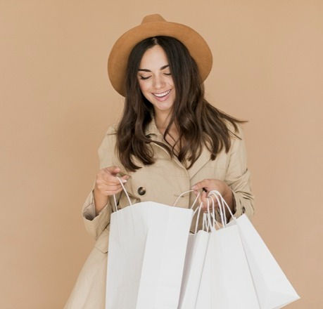 young-woman-looking-inside-shopping-bags