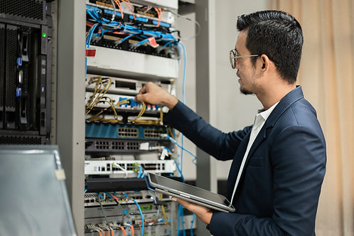 stock-photo-young-network-technician-holding-tablet-working-connecting-network-cables-serv
