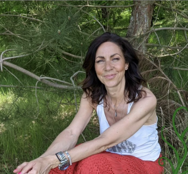 A white woman with brown wavy hair to her shoulders smiles at the camera. She is sitting on a grassy copse with a fir tree behind her. She wears a white vest and red harem pants with a silver watch visible on her wrist which is resting on her knees.