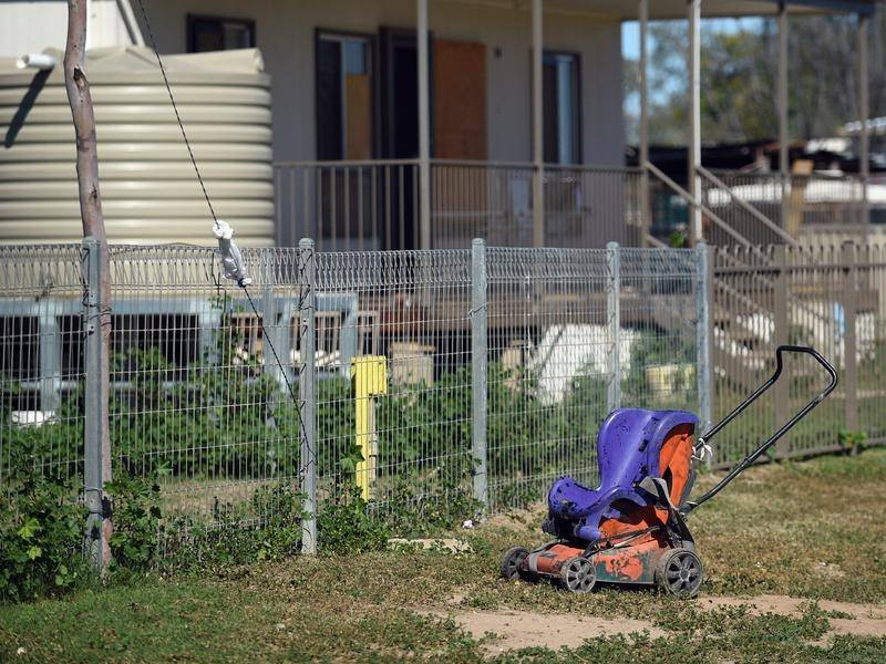 A stark image of a childs wheelchair sits abandoned beside a high wire fence indicating that children are being incarcerated.