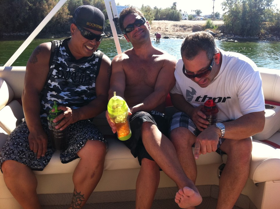 Three men are sitting laughing together in a boat, they are holding bottles of water and are enjoying the sunshine