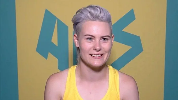 Robyn is a young white trans woman and sits smiling facing the camera, she has short lilac hair and wears a bright yellow vest. She sits in front of a yellow and green banner that reads AUS in green lettering.