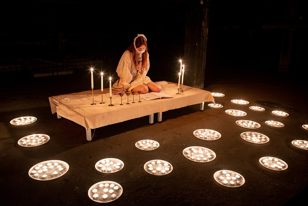 An artist sits on a table in a black room. She is white with long loose dark hair and wears a white dress and is gagged with white bandages. She is surrounded by candles of various heights.