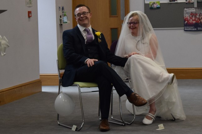 A couple on their wedding day smile broadly at the camera. The couple with downs syndrome both are seated on chairs, the white man wears a stylish navy suit with brown shoes and a bright yellow buttonhole. The woman wears a long white wedding dress, long veil and white mary jane shoes. Both of them wear glasses and look incredibly happy and relaxed.