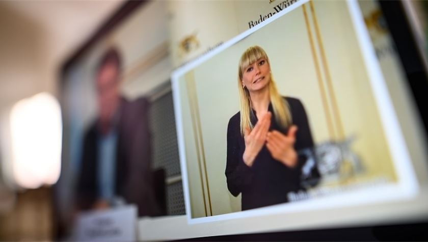 the image indicates a photo of someones laptop or computer screen, part of the screen is blurred out of vision. A young blonde sign language interpreter is visible on the screen. She is mid sign with two hands held in front of her.