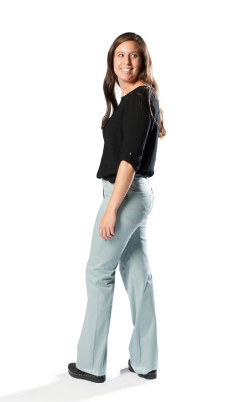 A white lady with long brown hair stands wearing a black mid sleeve top and mint green adaptive trousers for orthosis with a pocket detail on the back