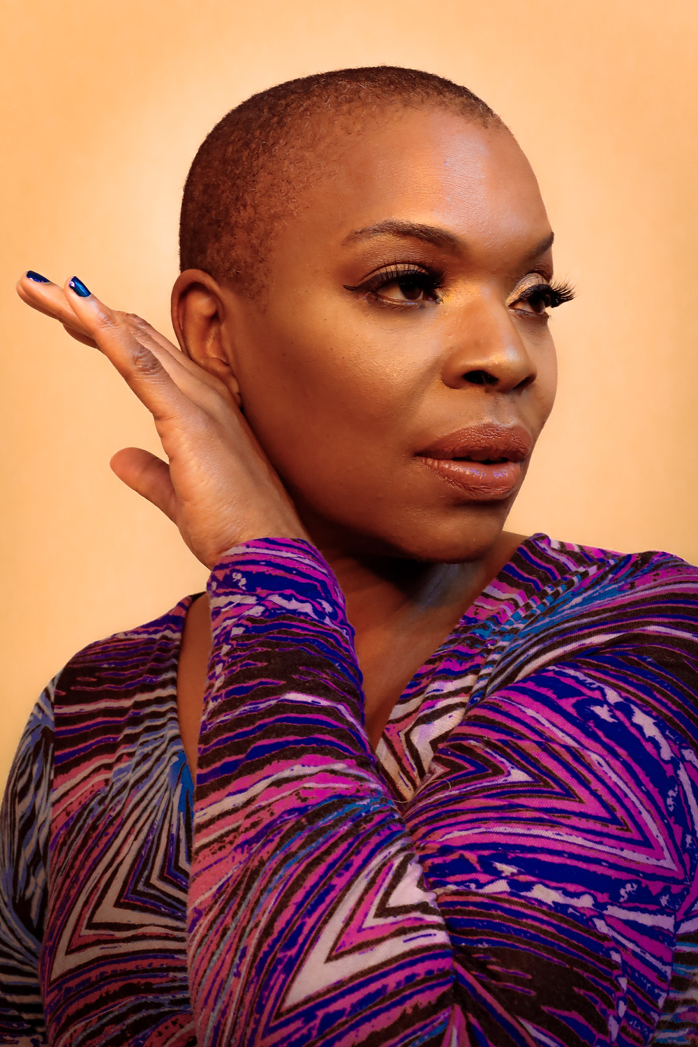 An image of Zazel, close up. She looks to the right with her hand resting against her face. She is a beautiful Black woman with cropped hair and wears a purple and pink top with striped patterns.