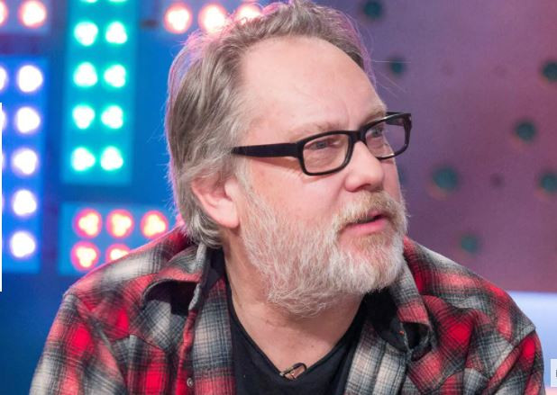 Vic is a white older gentleman. He has salt and pepper coloured tousled hair and a grey beard. He looks as if he is speaking to someone to his left. He wears black rimmed glasses, a red, white and grey checked shirt open with a black t-shirt underneath. Behind him are bright studio lights in red blue and green.