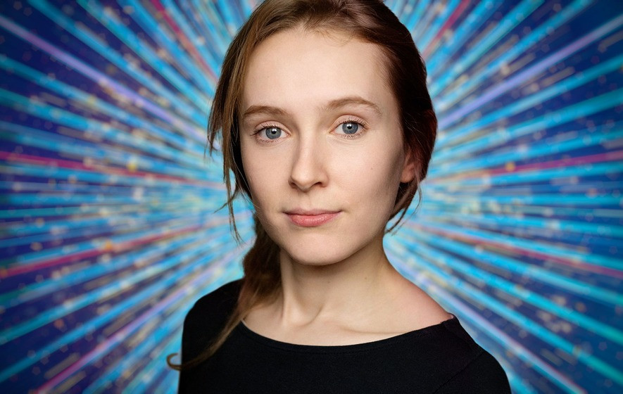 A young white woman with brown shoulder length hair looks at the camera. She wears a black tight scoop neck top and only her head and shoulders are visible. Behind her is a computer generated image of blue , red and white rays of light beaming behind her. Her hair is tied in a side plait over her right shoulder.